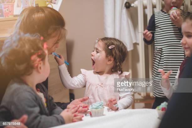 Babymeisje haar moeder vervoederen verjaardagstaart