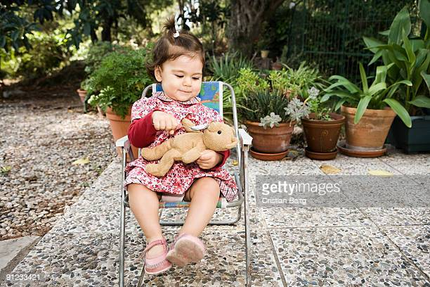 Baby girl feeding her teddy bear in garden