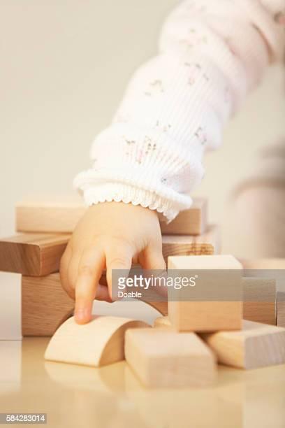 Baby Girl Hands on Wooden Block