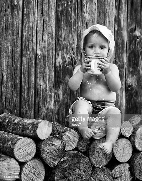 Baby girl holding a big metal cup