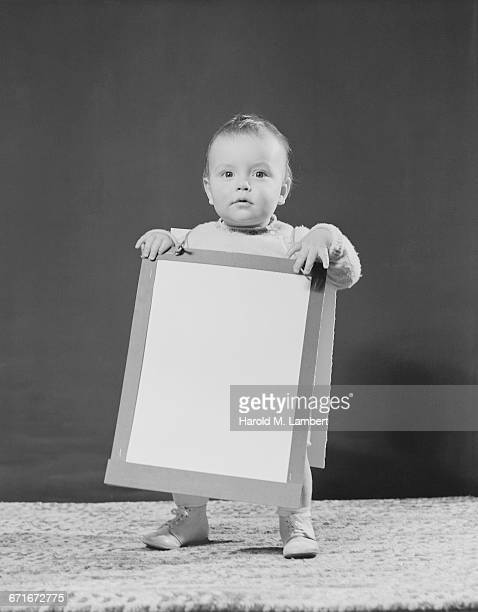 baby girl holding a blank cardboard sheet - {{ contactusnotification.cta }} 個照片及圖片檔