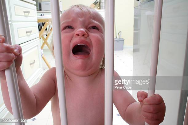 Baby girl (8-12 months) holding bars on safety gate, crying