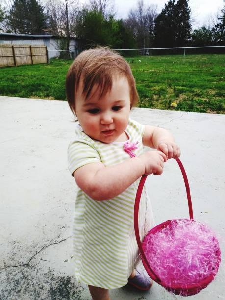 Baby Girl Holding Basket While Standing On Footpath