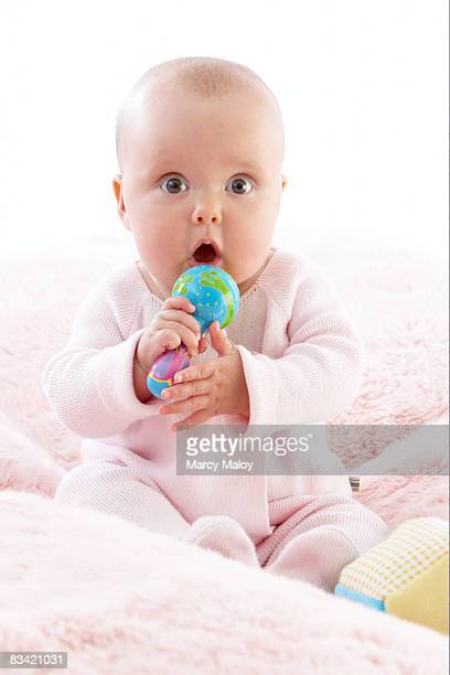 Baby girl holding bright rattle in her hands.