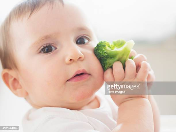 Baby girl (12-17 months) holding broccoli, Jersey City, New Jersey, USA