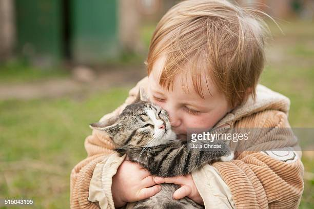 Baby girl holding cat and kissing