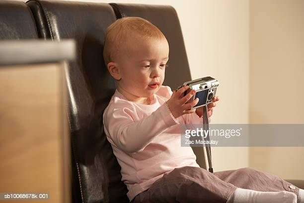 baby girl (6-11 months) holding digital camera sitting on chair - 6 11 months stock pictures, royalty-free photos & images