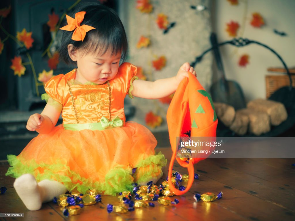 Baby Girl Holding Jack O Lantern Basket With Candies At Home : Photo