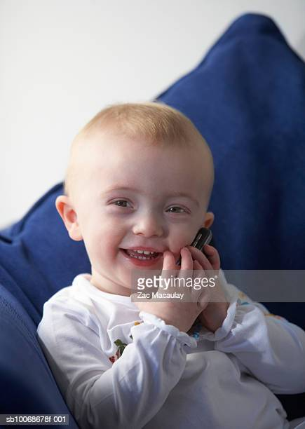baby girl (6-11 months) holding mobile phone against ear, portrait - 6 11 months stock pictures, royalty-free photos & images
