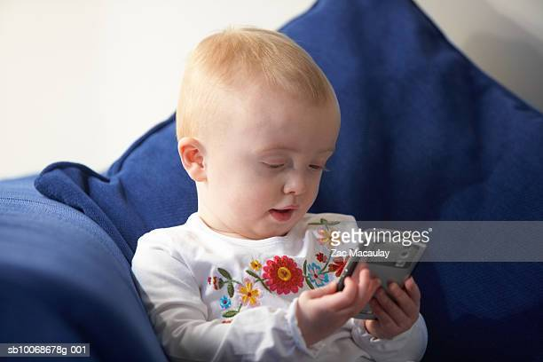 baby girl (6-11 months) holding palm top sitting on sofa - 6 11 months stock pictures, royalty-free photos & images