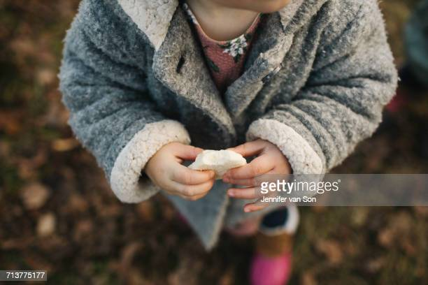 Baby girl holding piece of bread
