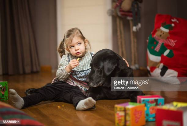 Baby girl hugging big black dog