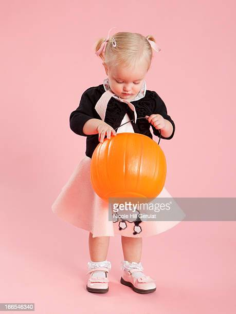 baby girl (12-17 months) in 1950s style costume, holding pumpkin lantern for halloween - poodle skirt stock photos and pictures
