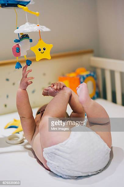 A baby girl in a diaper lying in a cot reaching up to a colourful mobile hanging above her.