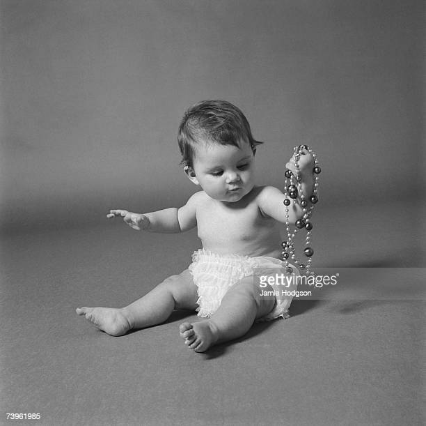 A baby girl in a frilly nappy holds a necklace of shiny beads 1965