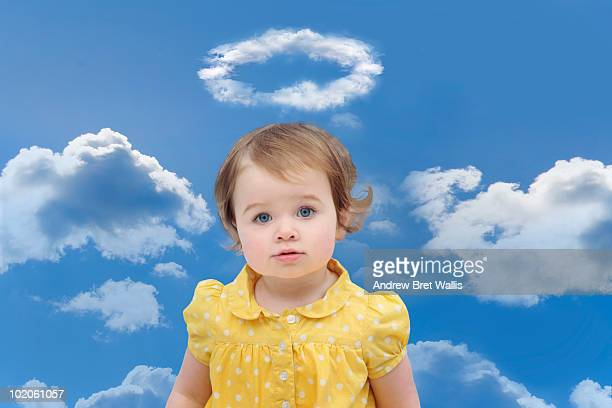Baby girl in a yellow dress under a cloud halo