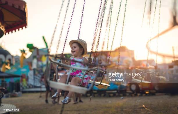 Ein kleines Mädchen in einem Vergnügungspark auf Kettenkarussell sitzt