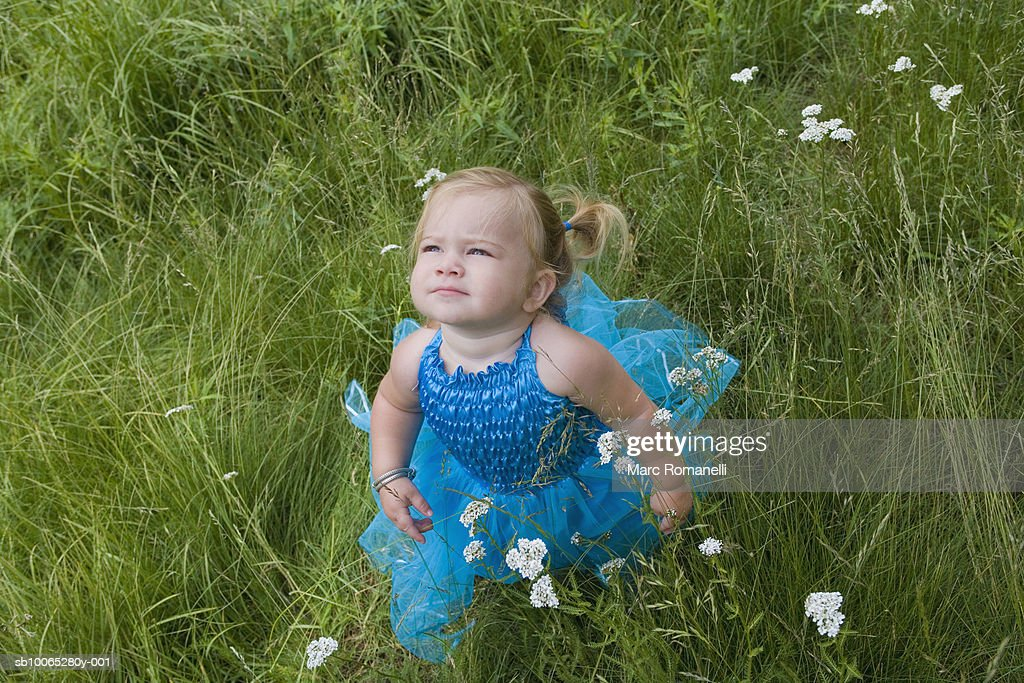 Baby girl (9-12 months) in blue dress in field : Foto stock