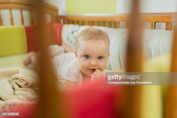 """baby girl in crib chewing hand - """"compassionate eye"""" stock pictures, royalty-free photos & images"""