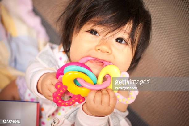 Baby girl in discomfort chewing on teething rings