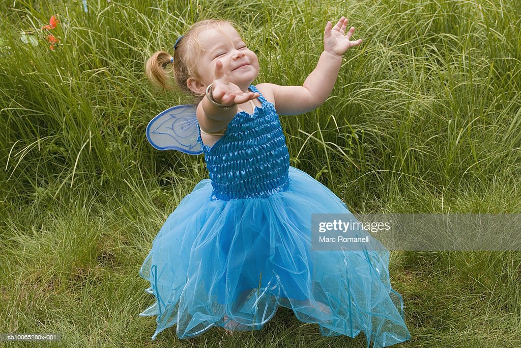 Baby girl (9-12 months) in fairy costume in grass : Foto stock