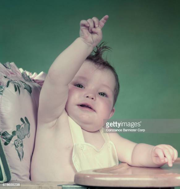 Baby Girl In High Chair Arm Up Pointing