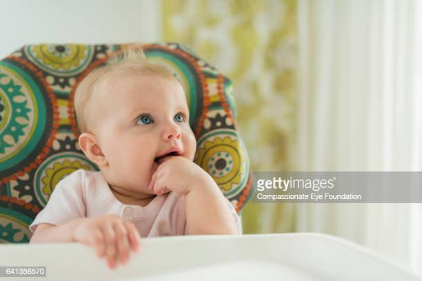 Baby girl in high chair chewing hand