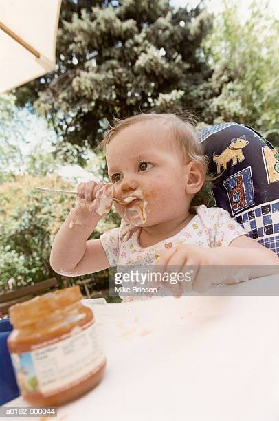 Baby Girl in High Chair Eating