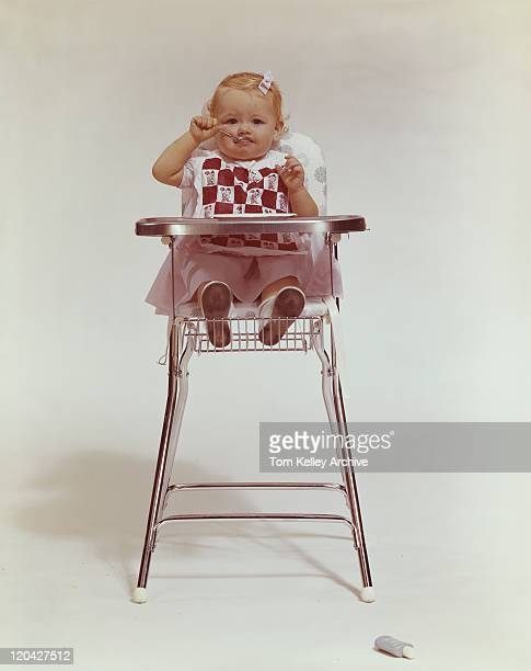 Baby girl in high chair eating with spoon, portrait