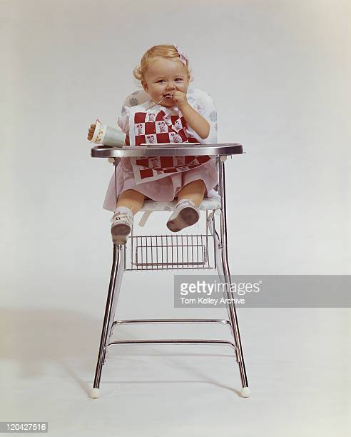 Baby girl in high chair holding disposable cup, smiling, portrait