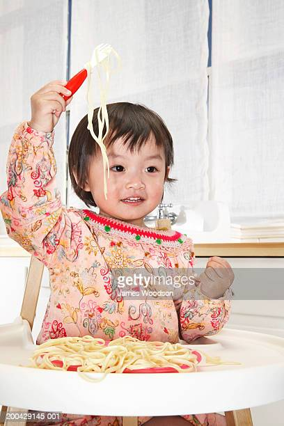 baby girl (18-24 months) in high chair holding pasta on fork, smiling - 18 23 meses fotografías e imágenes de stock