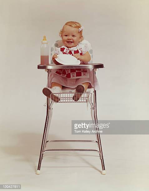 Baby girl in high chair holding plate, smiling