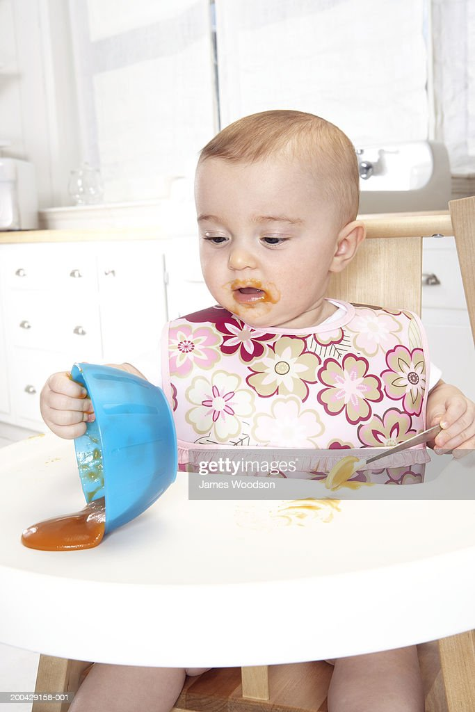 Baby girl (5-7 months) in high chair tipping bowl on tray : Stock Photo