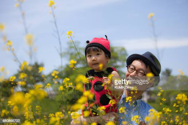 Baby girl in ladybird outfit and father enjoys weekend in flower garden