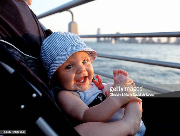 Baby girl (9-12 months) in pram by river, smiling, portrait