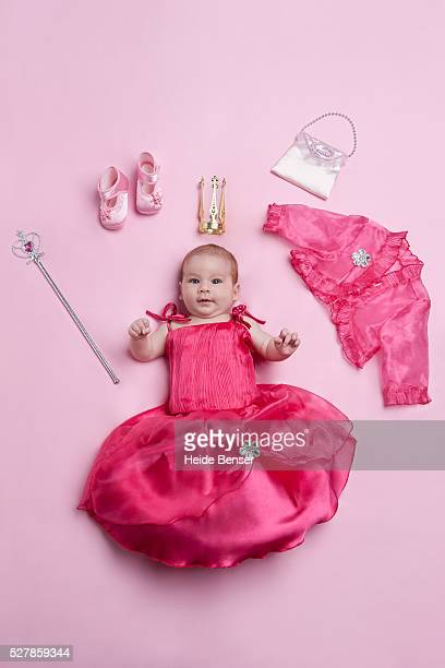 baby girl (6-11 months) in princess-dress lying on pink ground with accessories - 6 11 months stock pictures, royalty-free photos & images