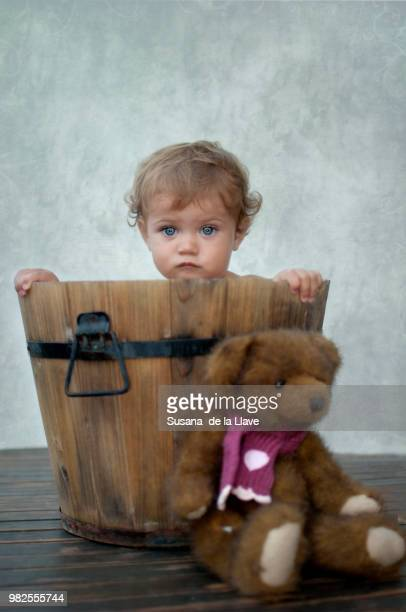 Baby girl (12-17 months) in wooden bucket