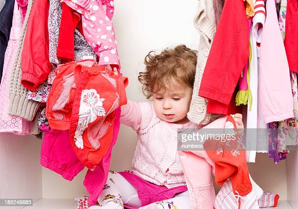 Baby girl inside a wardrobe with clothes
