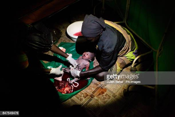 A baby girl is held by a midwife born onto tarpulin on the floorcompletely in the dark except for a torchlight in Bunj clinic which cares for people...