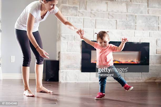 baby girl is walking her first steps with her mother - hot mom stock photos and pictures