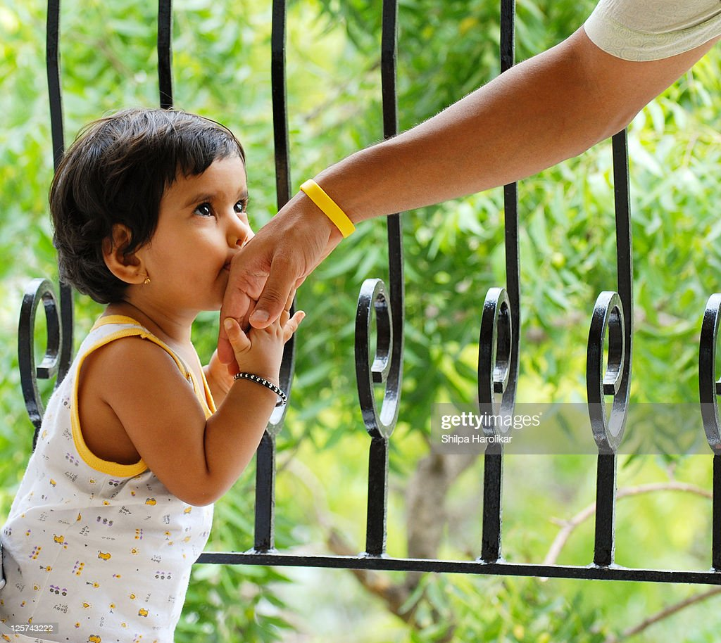 Baby girl kissing daddy hand : Stock Photo