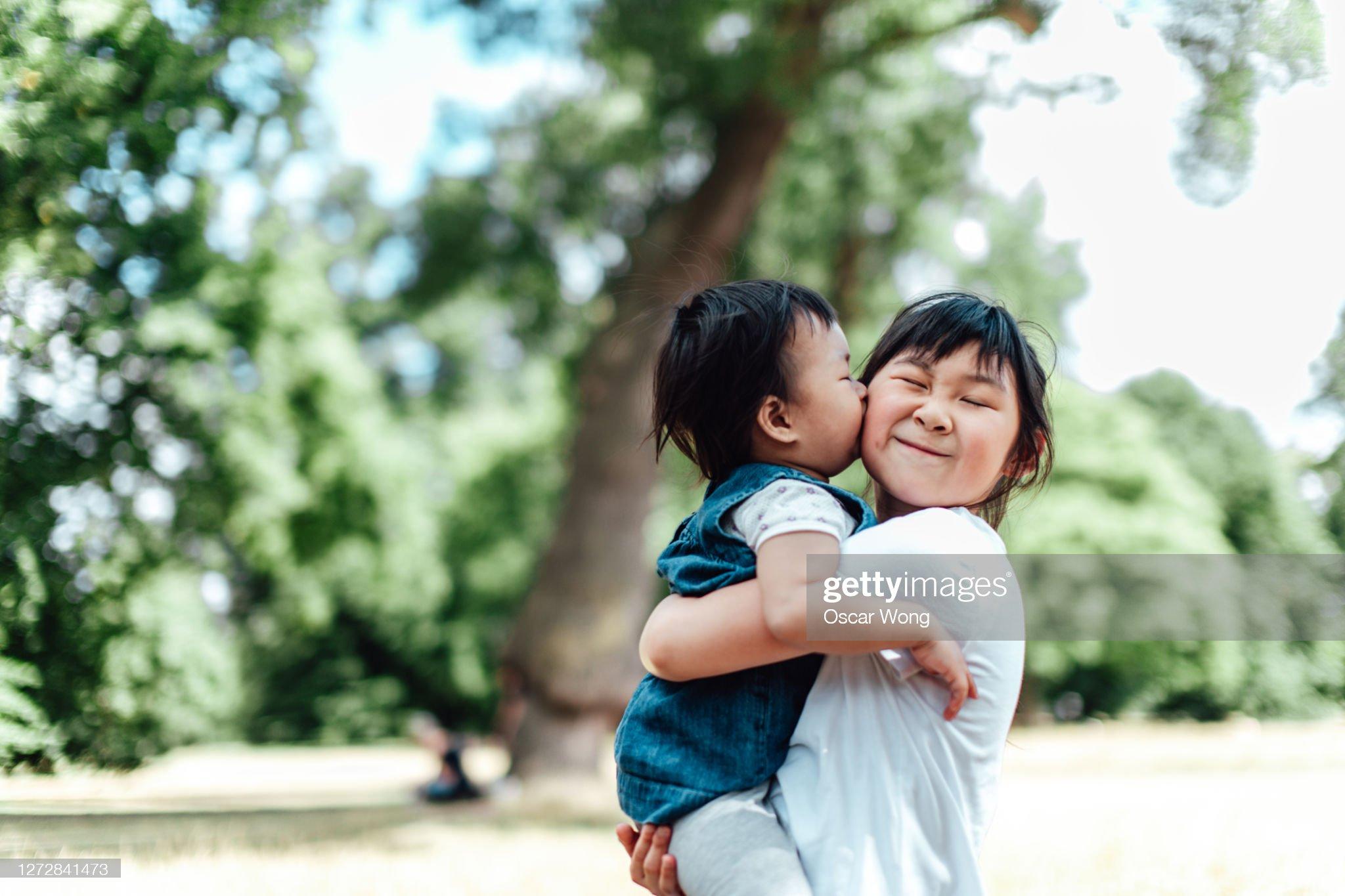 Baby Girl Kissing Her Sister On Cheek : 圖庫照片