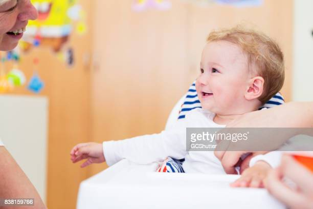 Baby girl laughing as she gets fed by her parents