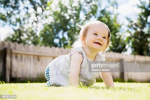Baby girl (6-11 months) laughing in backyard