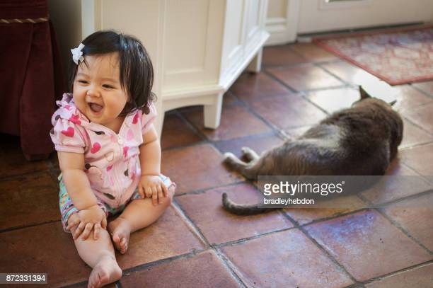 Baby girl laughing with pet cat