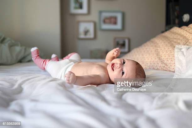 A baby girl laying on a bed