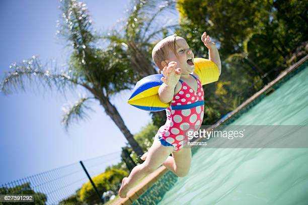 Baby girl leaps into a swimming pool