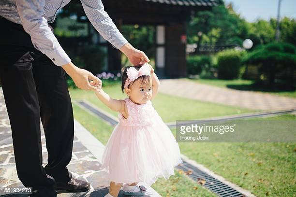 Baby girl learning to walk in garden