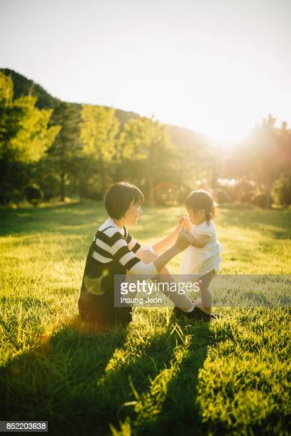 baby girl learning to walk supported by mother's hands. - korean culture stock pictures, royalty-free photos & images
