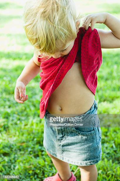 baby girl lifting shirt up, looking curiosly at abdomen - ombelico foto e immagini stock